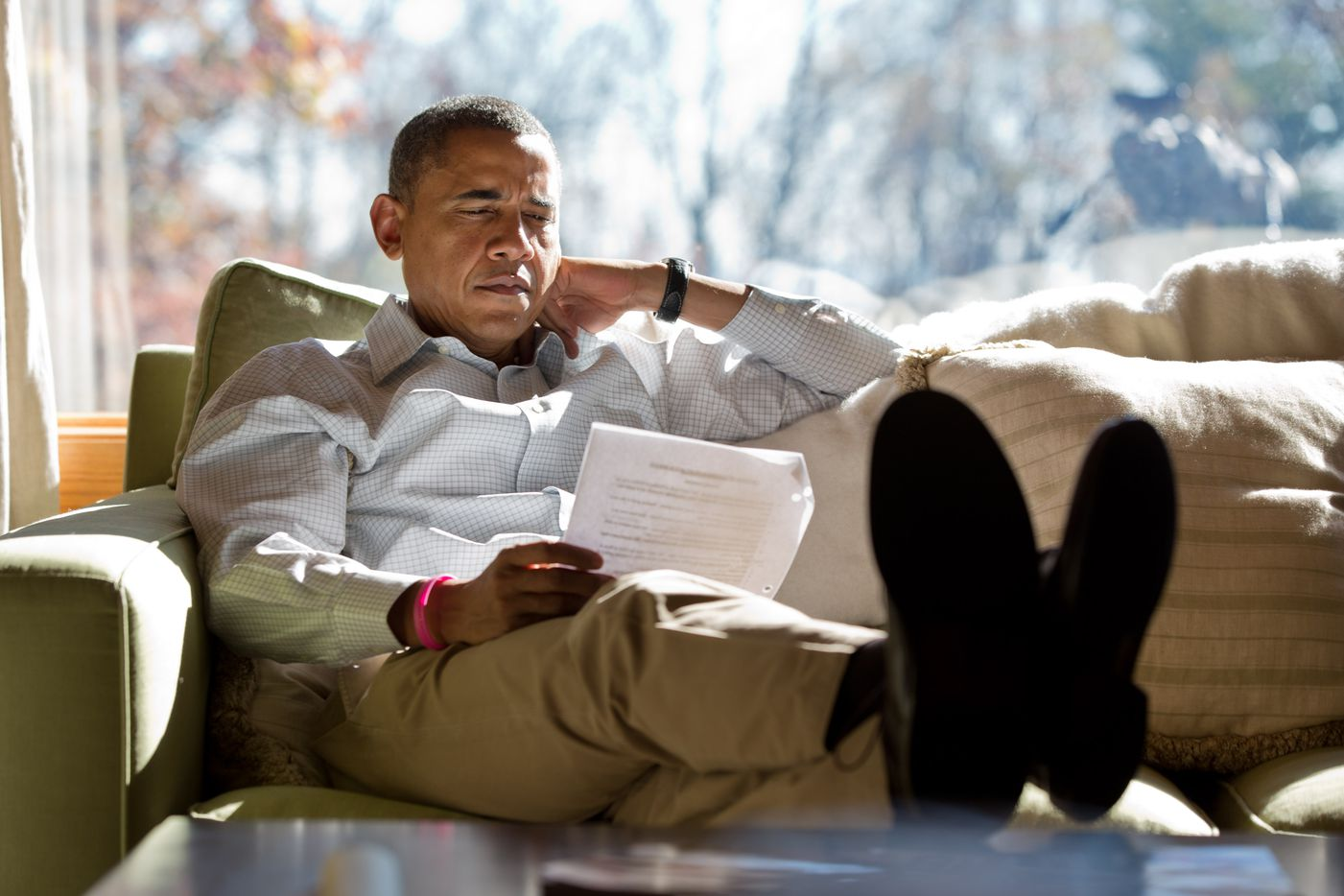 President Barack Obama reads briefing material while meeting with advisors inside his cabin at Camp David, on Sunday, Oct. 21, 2012.