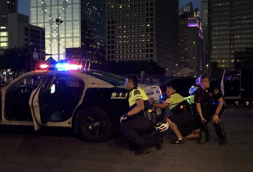 Dallas Police officers take cover behind a police cruiser as shots are fired following a Black Lives Matter rally July 7 in downtown Dallas. Five police officers were killed when Micah Johnson opened fire on the rally, injuring seven officers and two civilians. (G.J. McCarthy/The Dallas Morning News)