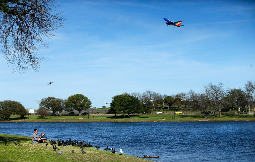 A Southwest Airlines jet takes off from Love Field as Roxie Murillo (left) of Dallas and Julian Ruiz feed the American Coots, Mallard ducks and pigeons along the Bachman Lake shoreline in Dallas on March 19, 2018.