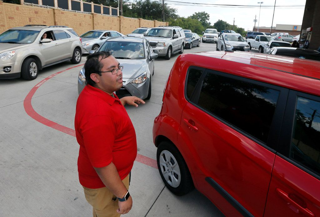 Marvin Andrade directs vehicles waiting in line to the next available gas pump at a Quik Trip station and convenience store in Dallas.