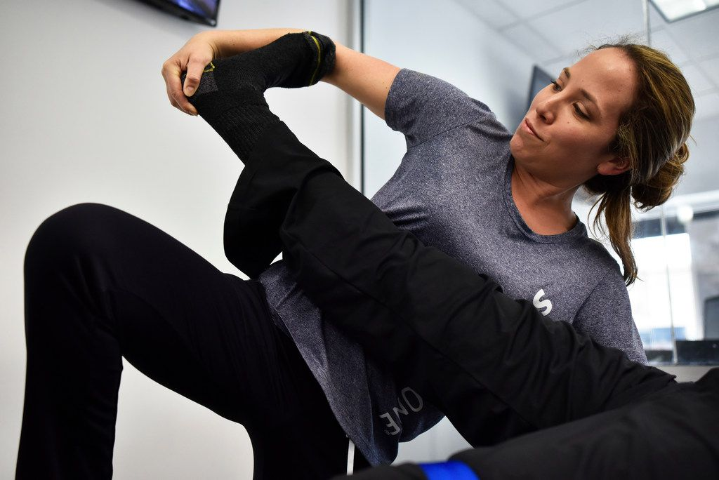 Stretch practitioner Danielle D'Alesio pulls on the leg and ankle of client Sergeant Jeff Wilson, of the Dallas County Sheriff Department, during a session at Stretch Zone in Dallas, Wednesday, March 13, 2019. Ben Torres/Special Contributor