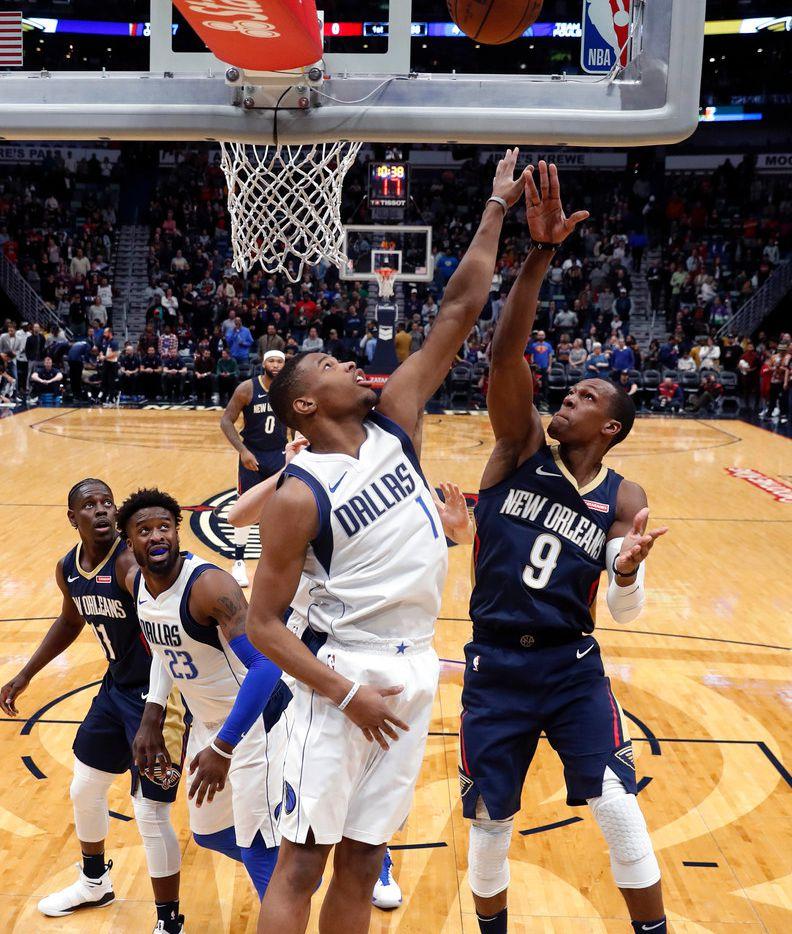 Dallas Mavericks guard Dennis Smith Jr. (1) battles for a rebound against New Orleans Pelicans guard Rajon Rondo (9) in the first half of an NBA basketball game in New Orleans, Friday, Dec. 29, 2017. (AP Photo/Gerald Herbert)