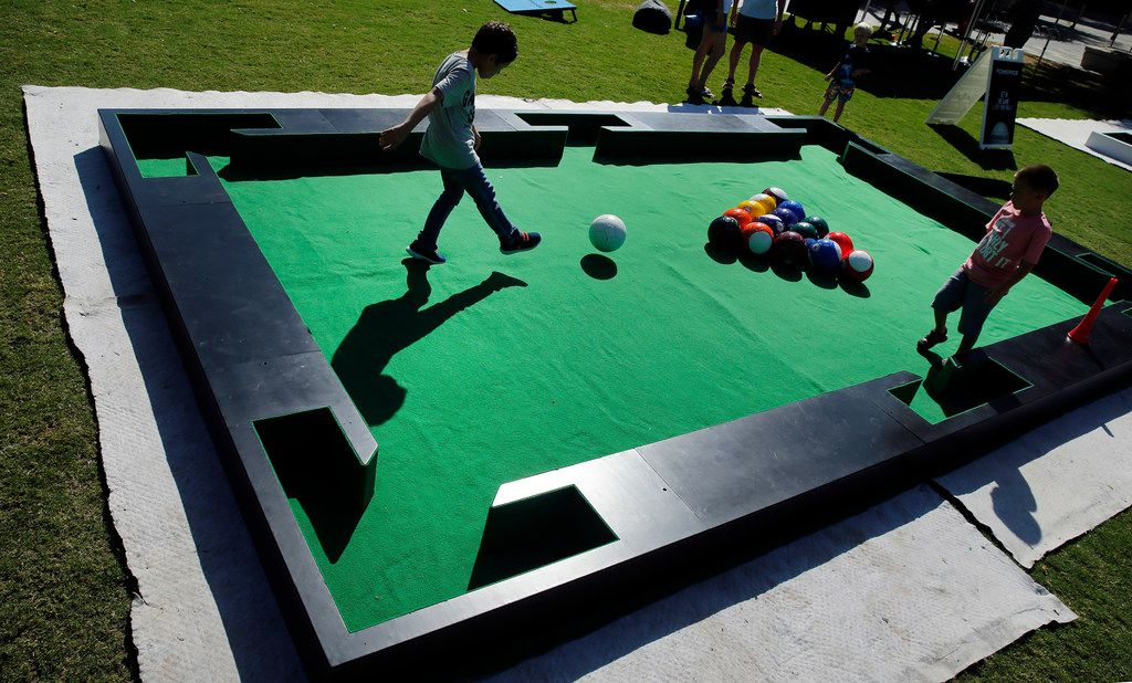 Oscar Gomez, 10, of Dallas kicks the soccer ball to break the 'pool' balls during a World Cup watching party at Klyde Warren Park in Dallas, Sunday, July 15, 2018. He was joined by his cousin Sebastian Gomez (right). France defeated Croatia, 2-1, in the championship game. (Tom Fox/The Dallas Morning News)