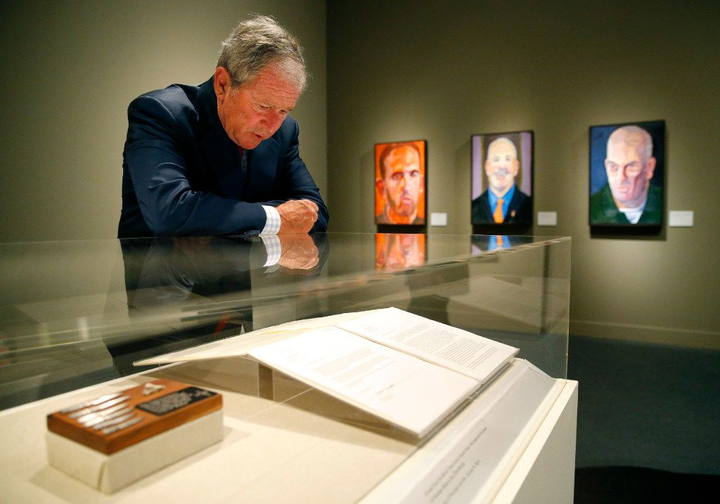 Former President George W. Bush reads one of the veteran letters on display of 'Portraits of Courage, A Commander In Chief 's Tribute To America's Warriors' exhibit which showcases his oil paintings at the George W. Bush Presidential Center in University Park.