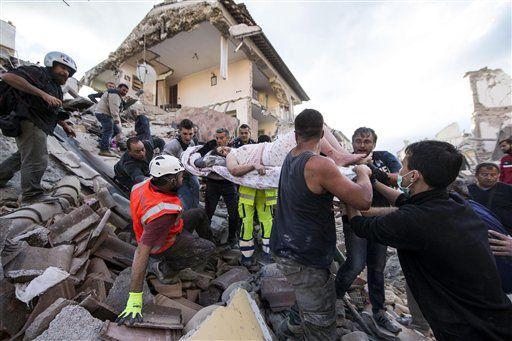 Una mujer es sacada a hombros en una camilla de debajo de los escombros tras el terremoto que sacudió Amatrice, una localidad en el centro de Italia, el 24 de agosto de 2016./AP