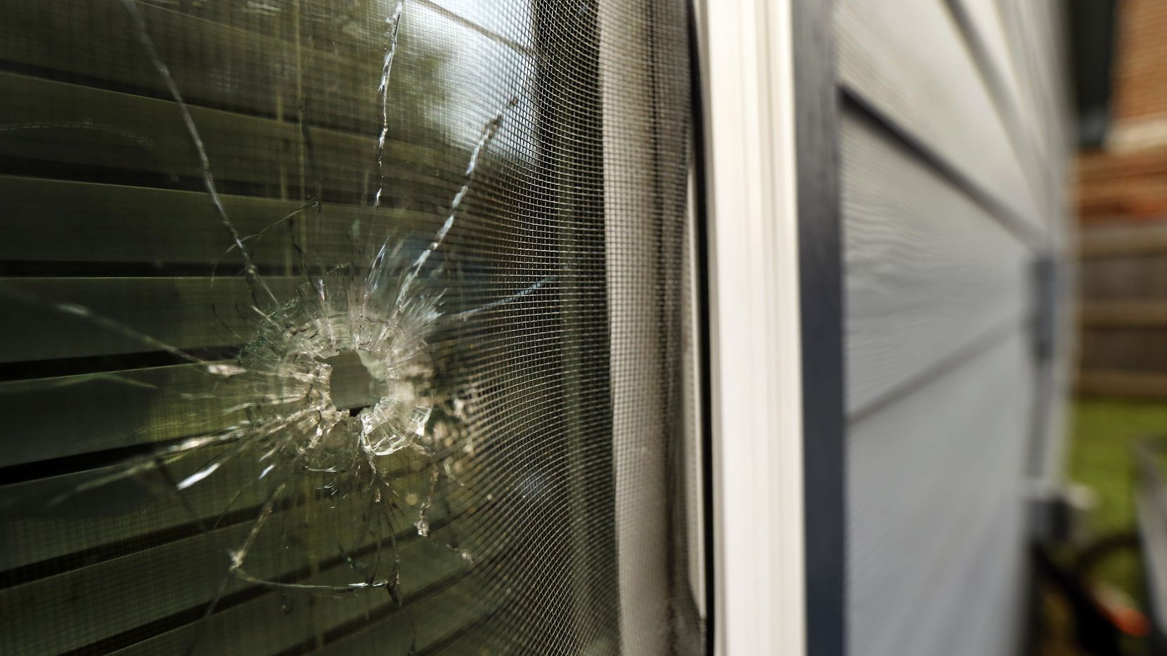 A bullet hole from the police officer's shot is seen in the rear window of Atatiana Jefferson's home on E. Allen Ave in Fort Worth, Tuesday, October 15, 2019 after former Fort Worth police officer Aaron Dean shot into the home and killed Atatiana Jefferson last weekend. In the wake of Fort Worth officer Aaron Dean shooting and killing Jefferson in her home, people have been stopping to leave flowers at a memorial in front of the house. (Tom Fox/The Dallas Morning News)
