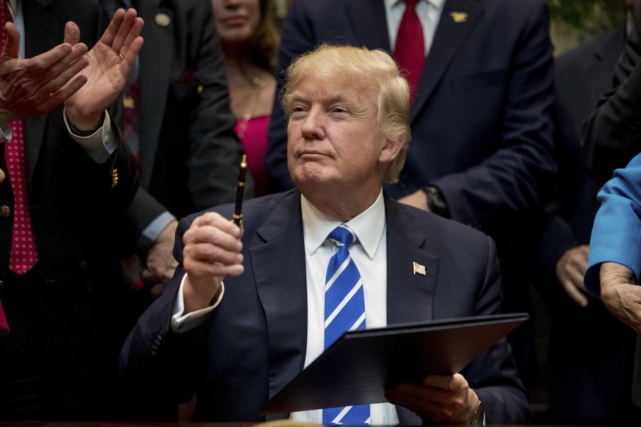 El presidente de Estados Unidos, Donald Trump, sostiene un bolígrafo para firmar una ley en la Roosevelt Room de la Casa Blanca, en Washington. (AP/ANDREW HARNIK)