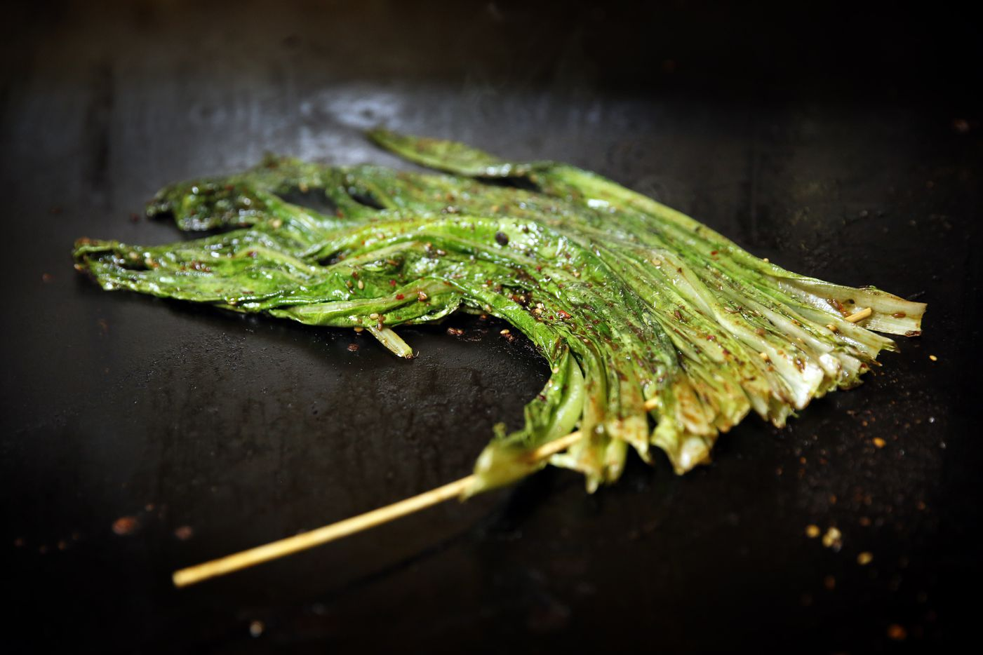 Skwered A-choy (Chinese greens) on a grill at FatNi BBQ (Tom Fox/Staff Photographer)