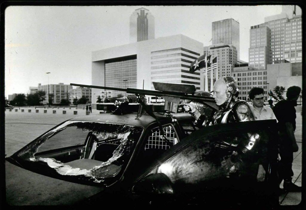 The Dallas skyline looms behind actor Peter Weller during a filming of RoboCop outside Dallas City Hall.