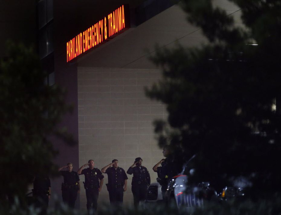Dallas police officers stood in salute as fallen officers were transported into UT Southwestern vans through a secure entrance at Parkland Memorial Hospital in Dallas early Friday.