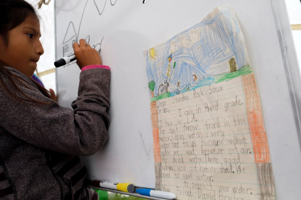 A girl draws a view of Standing Rock Sioux Reservation on the white board inside of a teepee at Oceti Sakowin Camp in North Dakota on Wednesday, Sep14th, 2016. Standing Rock has seen hundreds of whole families and activists visit, eager to take part in the historic gathering.  The camp offers teaching for children in the camp during the daytime. Construction has been halted after the Obama administration decision to suspend construction on a controversial oil pipeline in North Dakota.  (Jeenah Moon/Special Contributor)