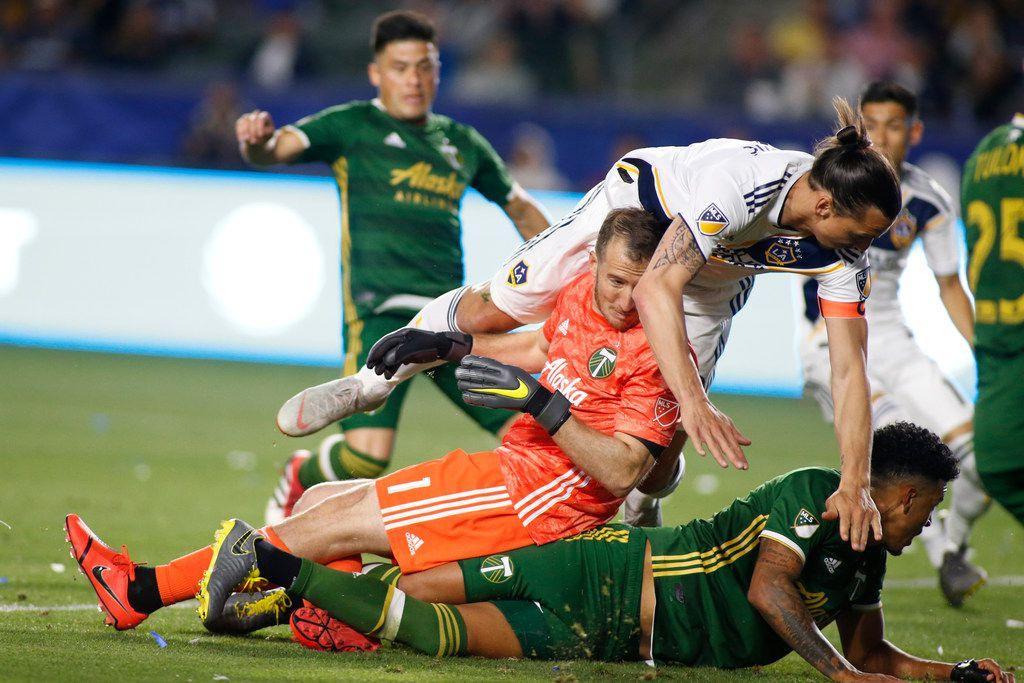 CARSON, CALIFORNIA - MARCH 31:  Zlatan Ibrahimovic #9 of Los Angeles Galaxy falls over Jeff Attinella #1 of Portland Timbers and Jeremy Ebobisse #17 of Portland Timbers during the second halfat Dignity Health Sports Park on March 31, 2019 in Carson, California. (Photo by Katharine Lotze/Getty Images)