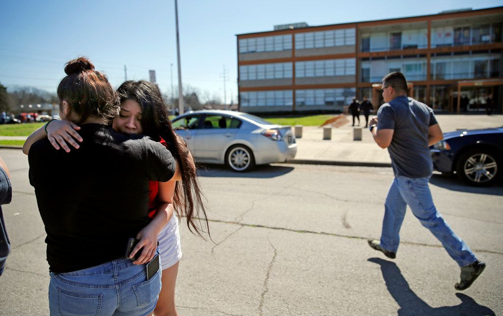 Juanita Ortiz is comforted by her sister Peta Hernandez as parents arrive at E.B. Comstock Middle School in southeast Dallas.