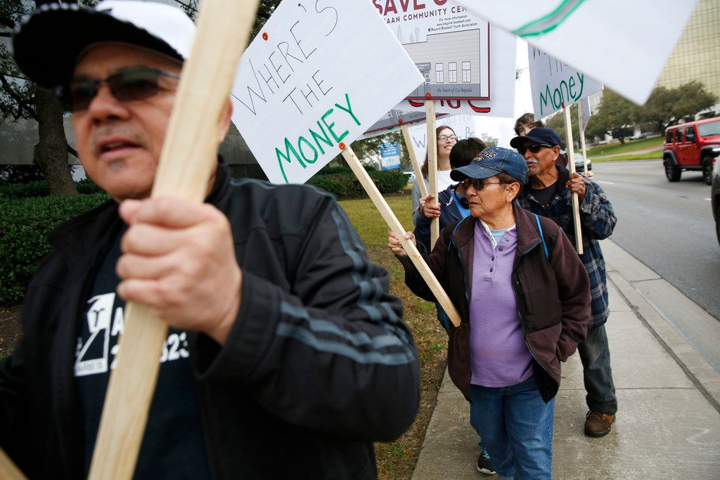 in February, West Dallas residents, including Juanita Hernandez (purple), protested outside the Mockingbird Lane offices of the Lucious Williams Foundation.
