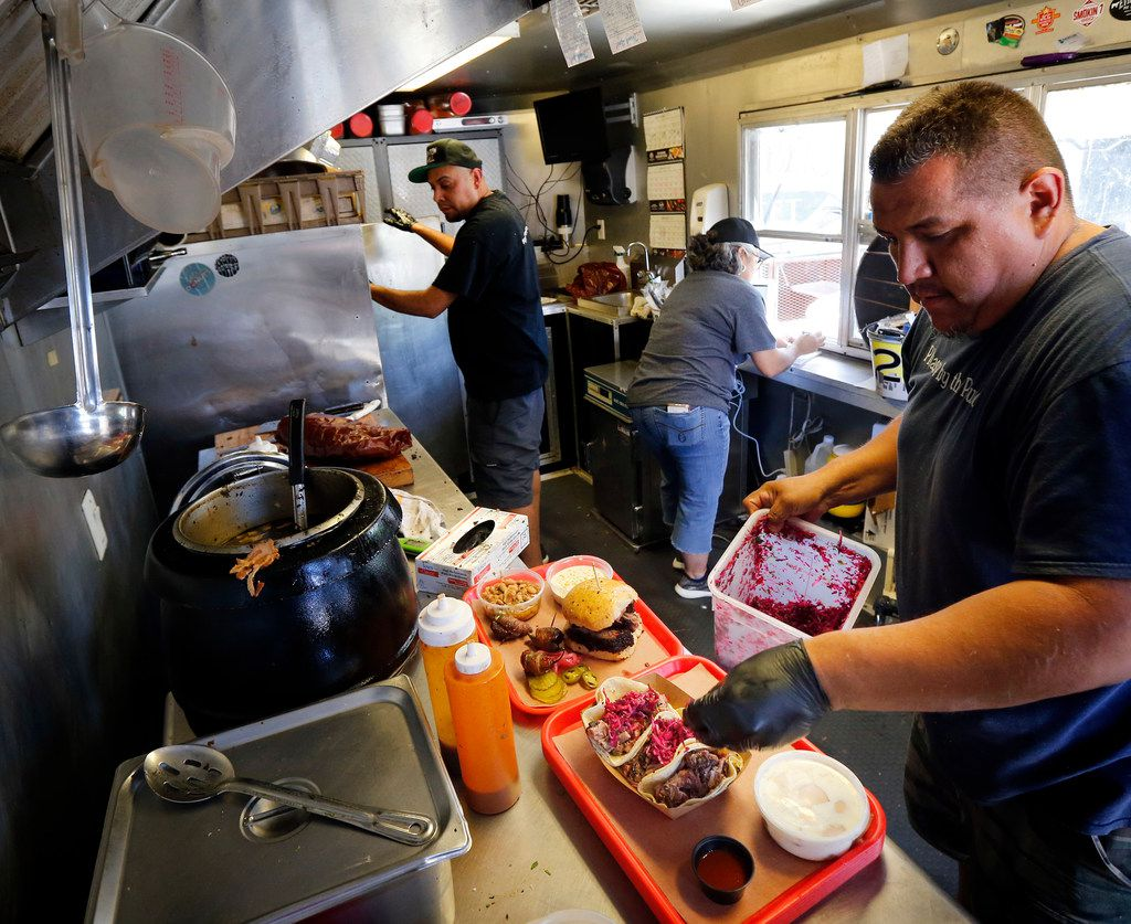 Panther City BBQ co-pitmasters Chris Magallanes prepares brisket tacos and sandwiches with Ernie Morales in their trailer adjacent to The Republic Street Bar on Hattie St. in Fort Worth, Saturday, April 19, 2019. (Tom Fox/The Dallas Morning News)