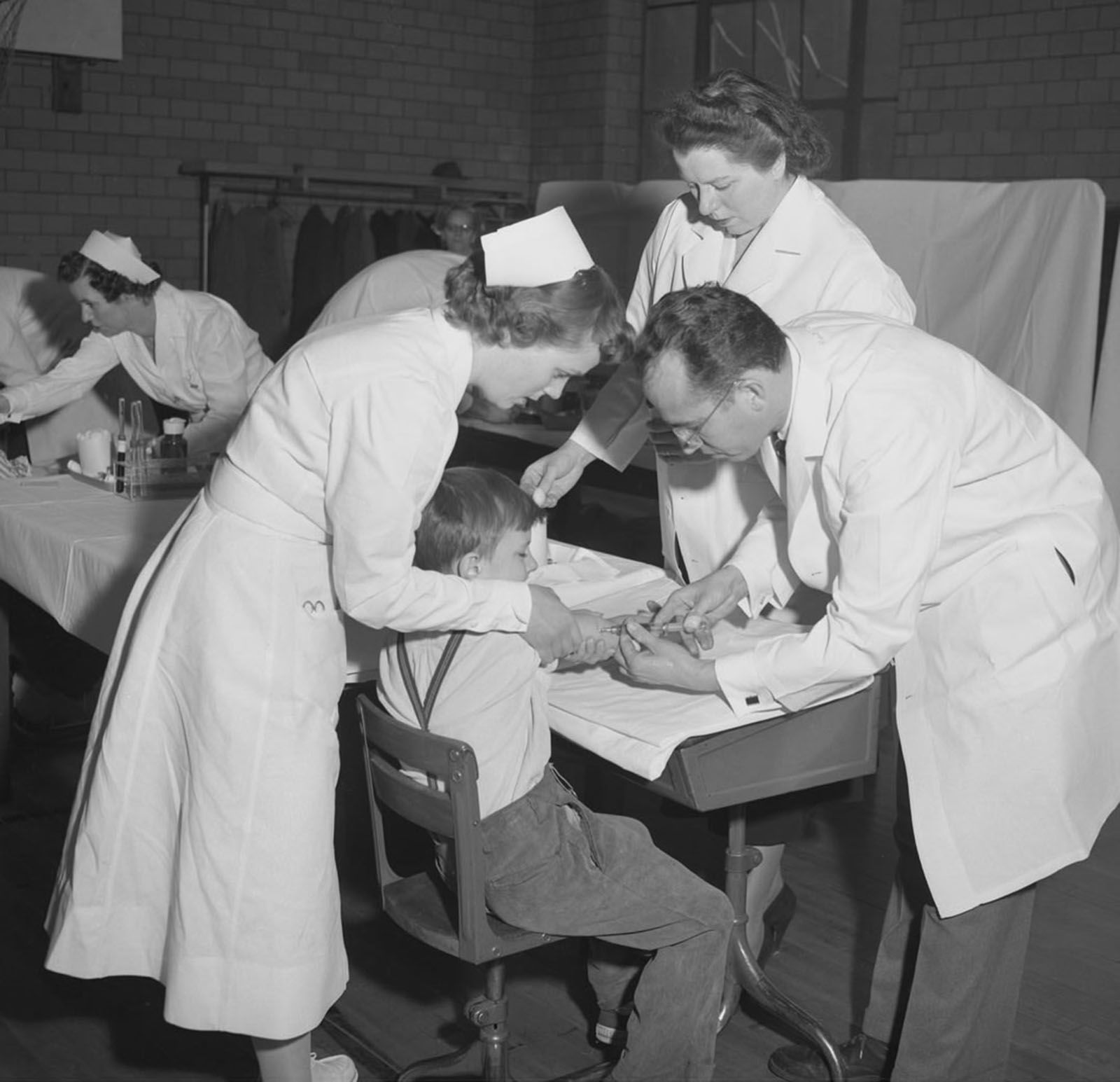Dr. Jonas Salk (right), the scientist who developed the first polio vaccine, administers an injection to a boy in Pittsburgh. The Salk vaccine came into use in 1955. The oral vaccine was developed by Dr. Albert Sabin and was used on the public starting in 1961. (File Photo/The Associated Press)