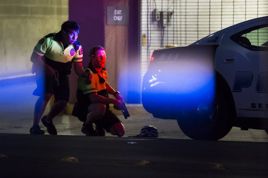 Dallas Police officers take cover behind a vehicle on Lamar Street after shots were fired during a Black Lives Matter rally in downtown Dallas on Thursday, July 7, 2016. As the rally and march were winding down, Micah Xavier Johnson, 25, opened fire in an attack that killed five police officers and wounded seven other officers and two civilians. (Smiley N. Pool/The Dallas Morning News)