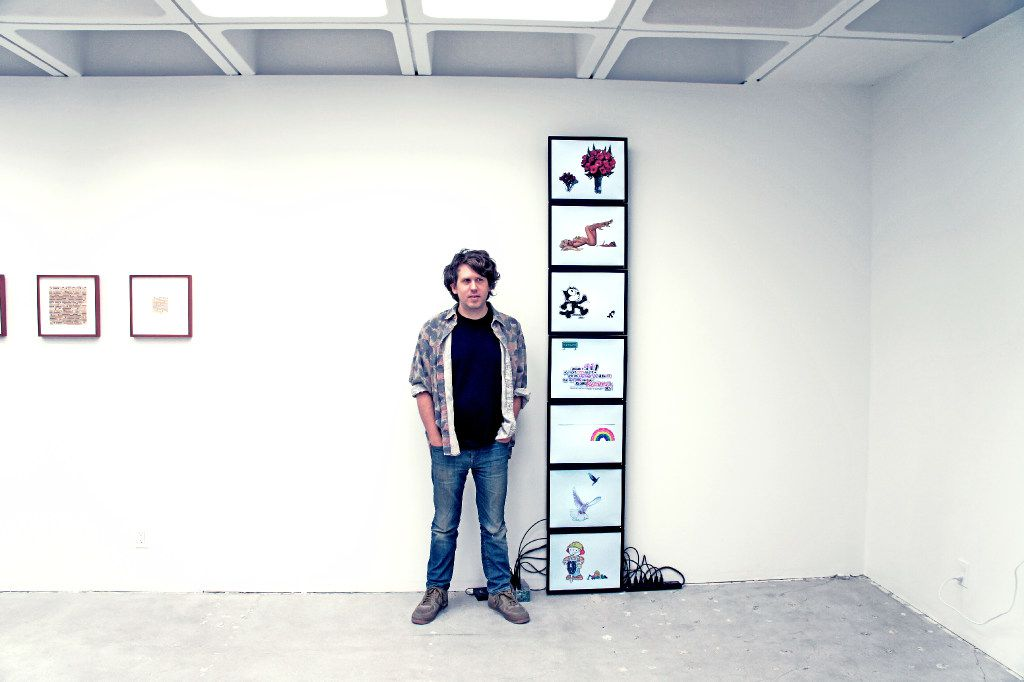 """Paul Slocum co-founded the original And/Or Gallery in Dallas with Lauren Gray in 2006. Seven years after it closed, he reopened the gallery in Pasadena, Calif., this winter. He is shown here in the new space beside Olia Lialina and Dragan Espenschied's work, """"Olia's and Dragan's Comparative History of Classic Animated GIFs and Glitter Graphics,"""" 2007, 7-channel video without sound."""