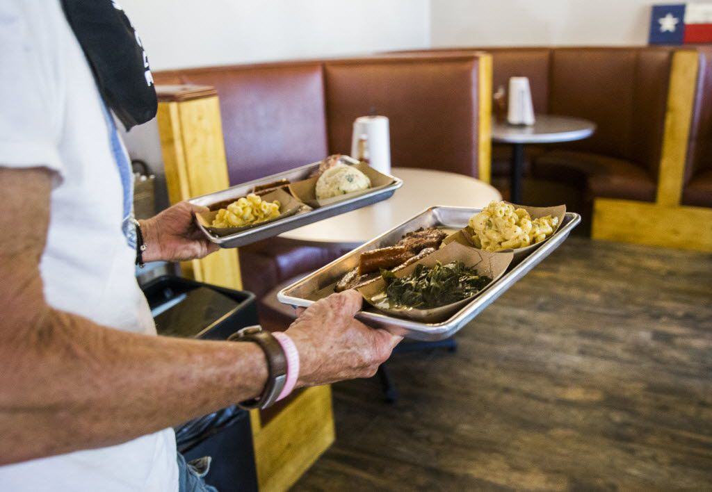 Jeff Knipper carries his order to his table at Heim Barbecue's new location on Saturday, August 6, 2016 on W. Magnolia Ave. in Fort Worth.