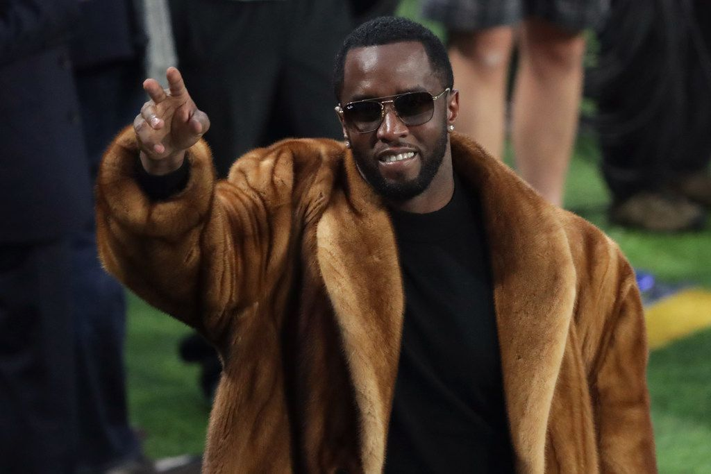 """Fresh dressed: Rapper Sean """"Diddy"""" Combs waves to the crowd during warm-ups prior to Super Bowl LII between the New England Patriots and the Philadelphia Eagles at U.S. Bank Stadium on February 4, 2018 in Minneapolis, Minnesota."""