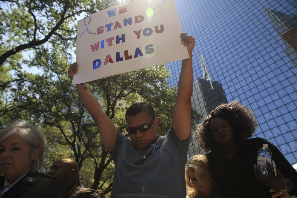 A sign of support among the crowd gathered for a vigil at Thanks-Giving Square in Dallas, near the site where five police officers were shot dead and seven more were wounded the night before, July 8, 2016. Religious leaders and other speakers, many wearing blue and yellow ribbons in solidarity with police, called for unity and peace in the wake of the mass shooting. (Dylan Hollingsworth/The New York Times)