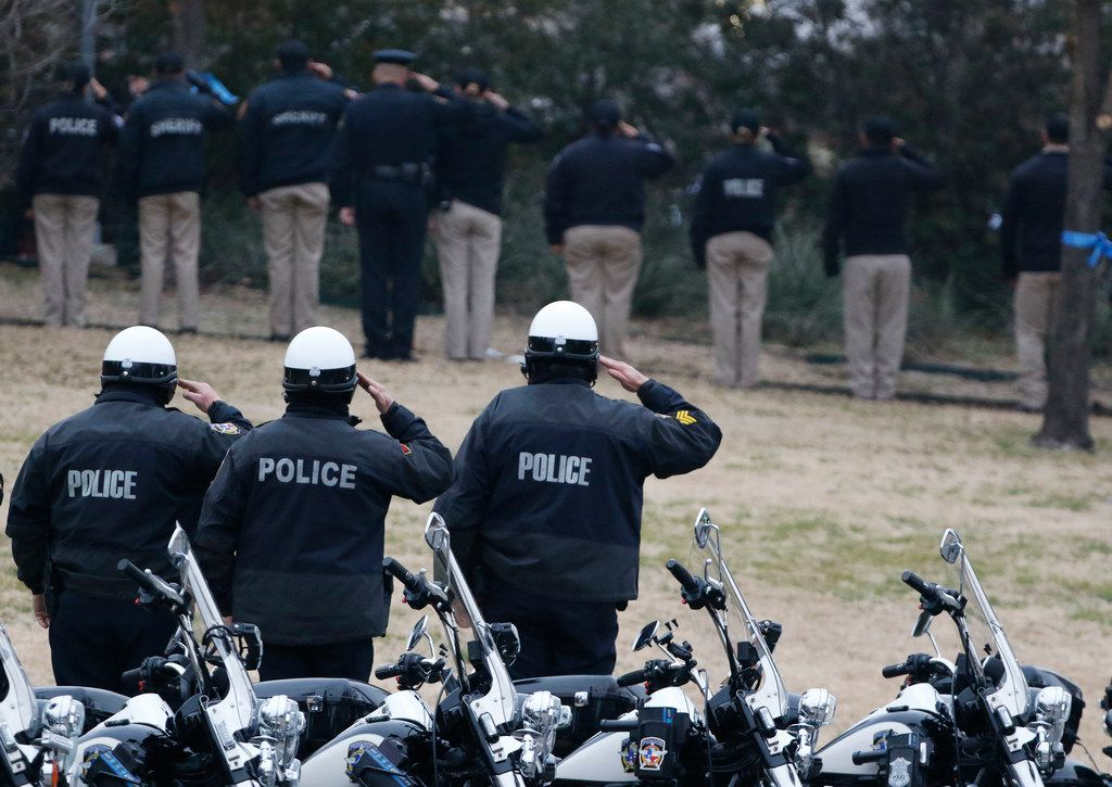 Law enforcement officer's salute during taps for Richardson police officer David Sherrard outside of Watermark Community Church in Dallas, Texas, Tuesday, February 13, 2018. Sherrard was fatally shot Wednesday, Feb. 8, 2018 at an apartment complex. (David Woo/The Dallas Morning News)