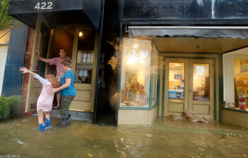 Majka Woods (right) and her daughter Anneli Kucera play in the flooded sidewalk as Tim Thompson watches from the step of their residence in the historic Strand District. The city of Galveston, Texas was flooded from punishing overnight rains from Tropical Storm Harvey which passed by the island, Tuesday, August 29, 2017. Since the winds were out of the north, surge also came over the piers adding to the flooding. (Tom Fox/The Dallas Morning News)
