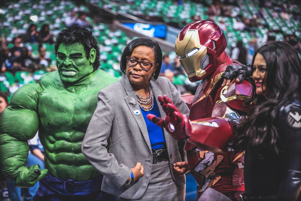 Mavericks CEO Cynt Marshall is flanked by the Incredible Hulk, Iron Man and the Black Widow at a Mavs game.