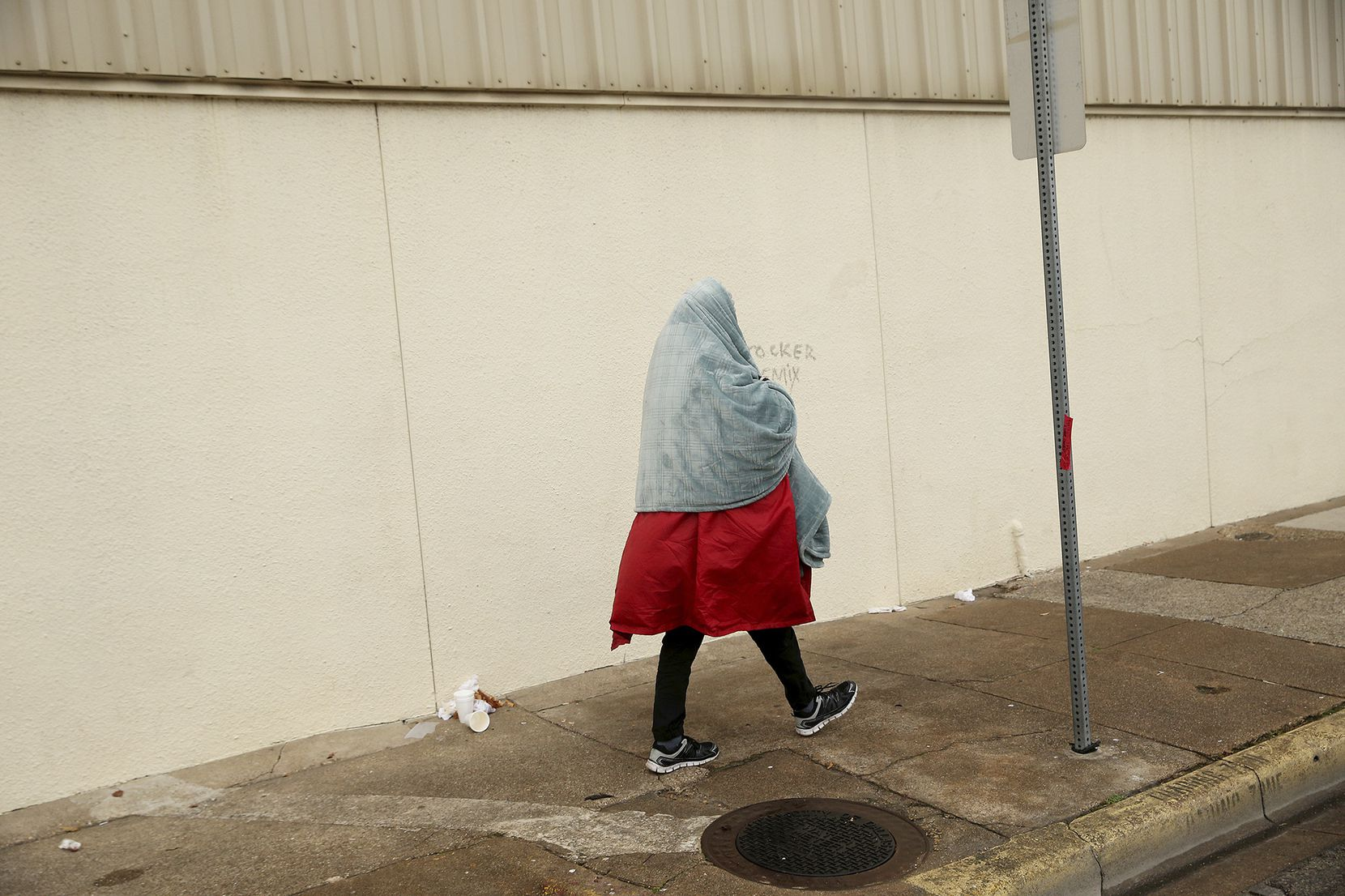 A man covered in a blanket walked along Cadiz Street as the homeless population prepared Saturday for the arrival of bitter cold temperatures in downtown Dallas.