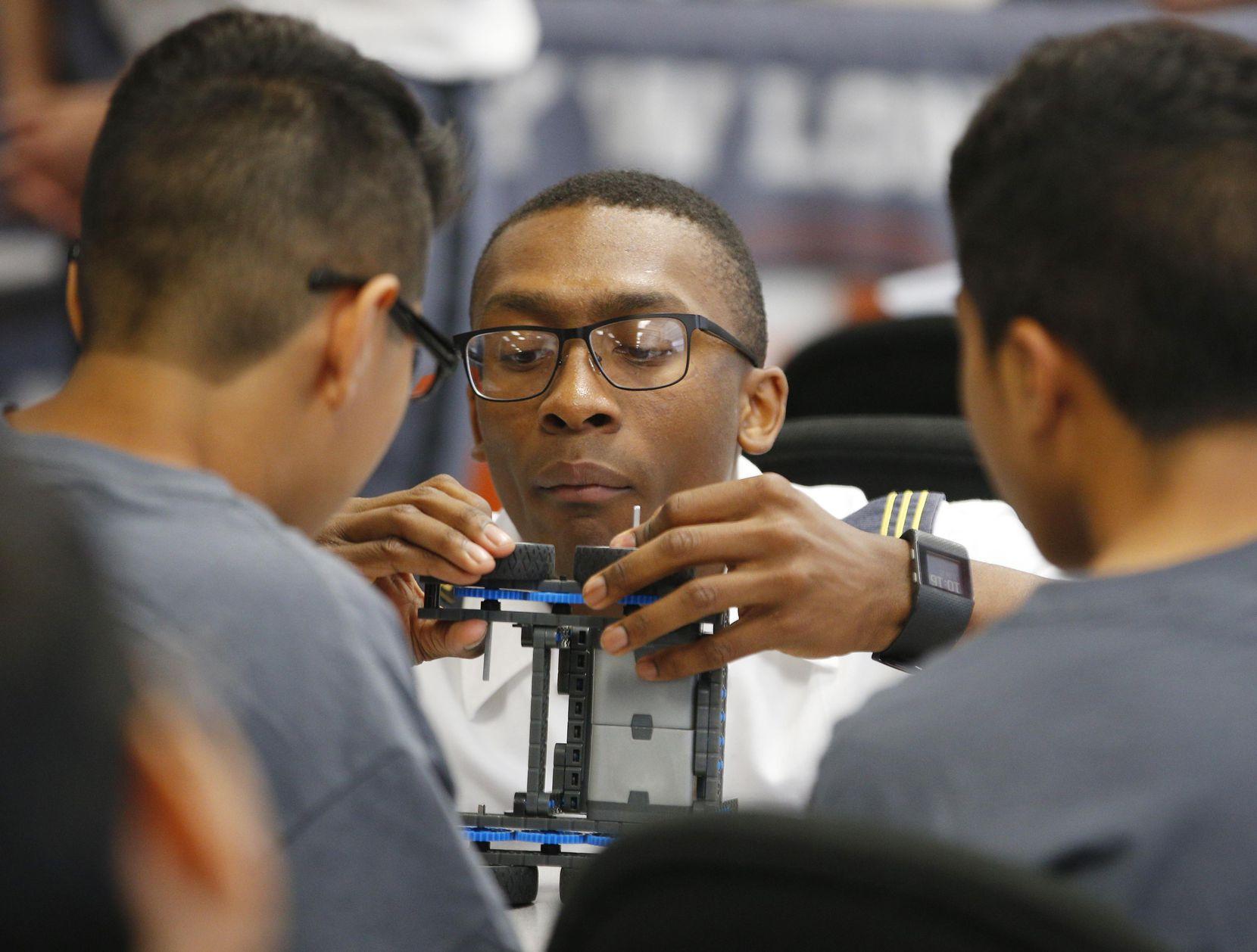 James Grays, un cadete de Westpoint, ayuda a Mauricio Pantoja, de 12 años, y Christian Orozco, de 15, a construir un robot VEX, durante un campamento de verano organizado por el distrito de Dallas. NATHAN HUNSINGER/DMN
