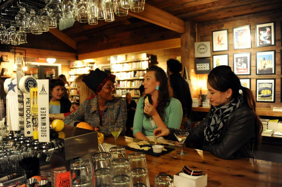 Chesley Antoinette, Cat Cole, and Pilar Zornosa sit at the bar, sip cocktails and eat cheese during the book signing of 'Mad Men Carousel' written by movie and television critic Matt Zoller Seitz. The Wild Detectives hosts book signings and social events regularly.