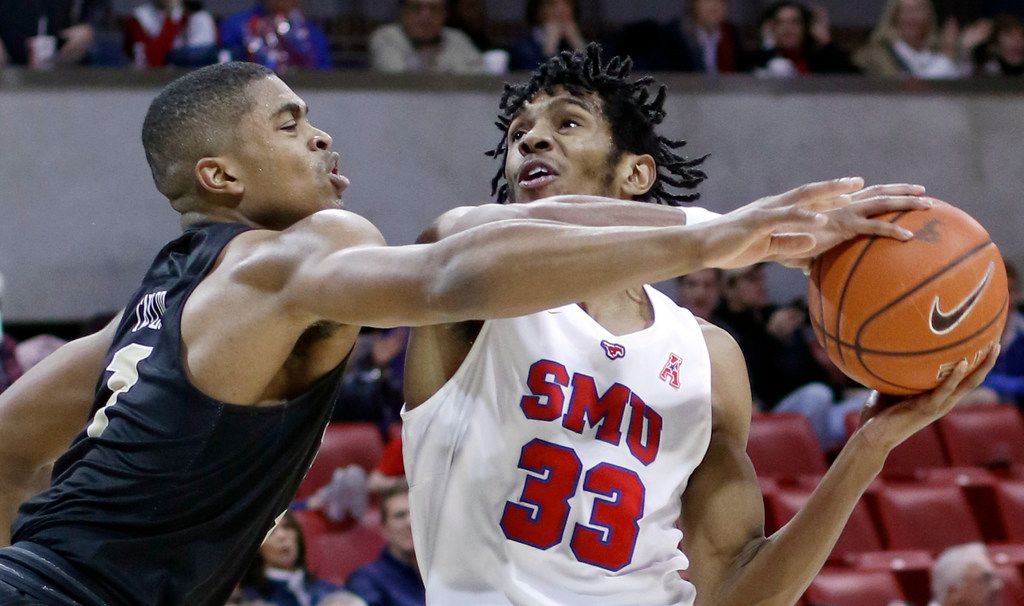 SMU guard Jimmy Whitt Jr. (33) drives strong to the basket against the aggressive defense of UCF guard BJ Taylor (1) during second half action. The two teams  played their NCAA Division 1 mens basketball game at SMU's Moody Coliseum in Dallas on February 10, 2019. (Steve Hamm/ Special Contributor)