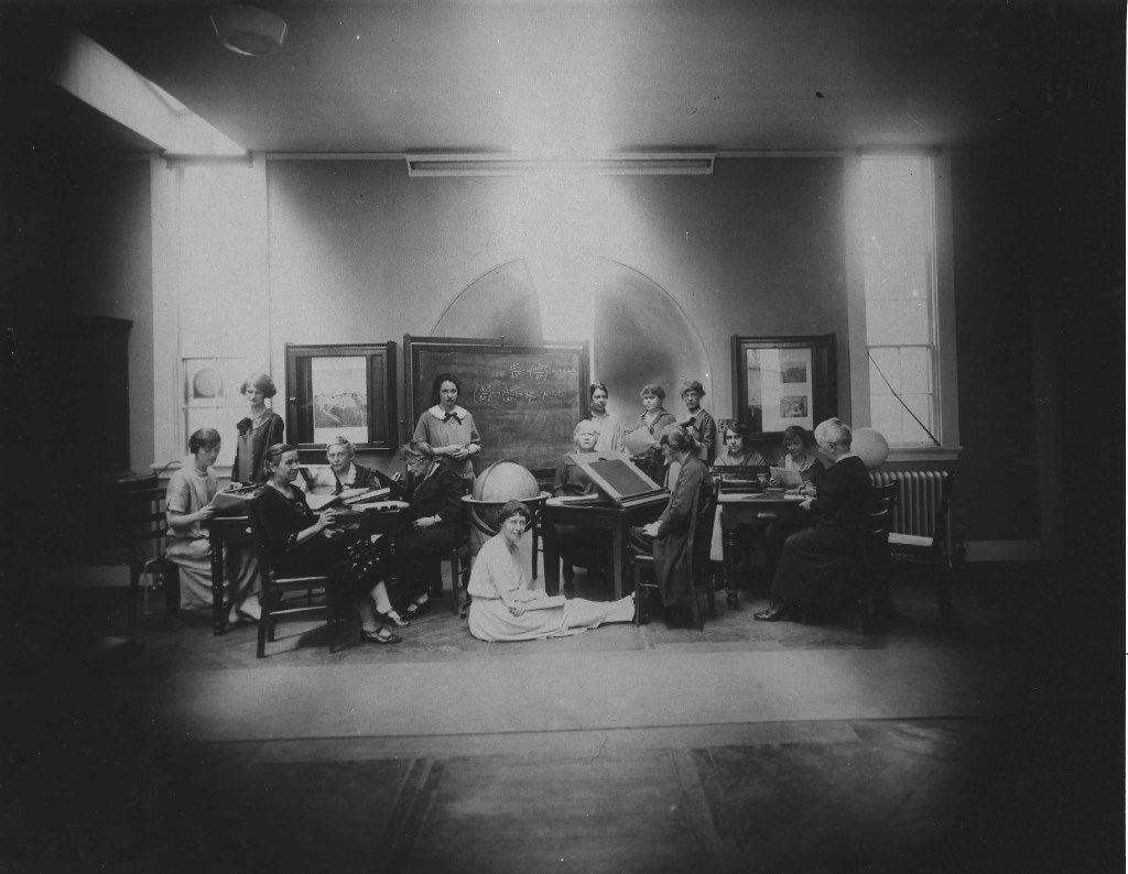 Margaret Harwood sat on the floor for this posed tableau taken on May 19, 1925. Harvia Wilson is at far left, sharing a table with Annie Cannon (too busy to look up) and Antonia Maury (left foreground.) The woman at the drafting table is Cecilia Payne. From The Glass Universe,  by Dava Sobel.