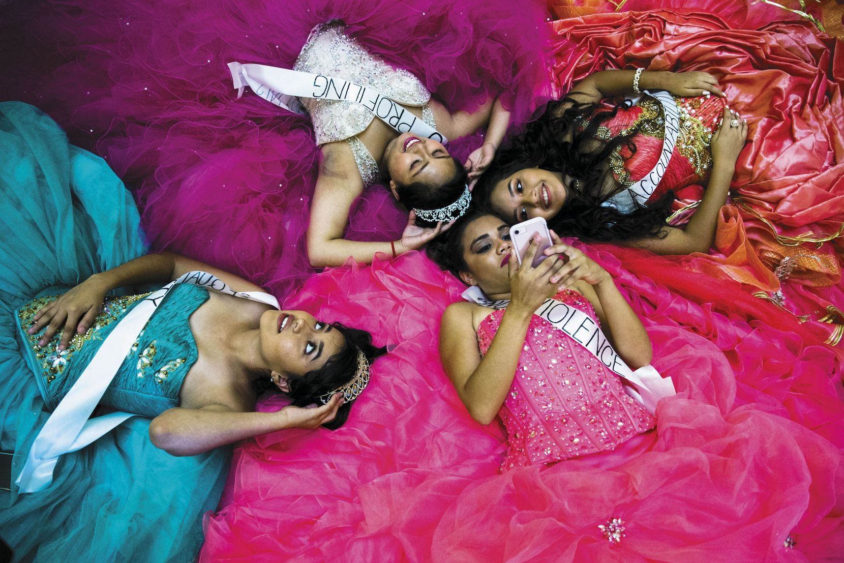 Clockwise from left: Evelyn Macias, 16, Viridana Sanchez, 16, Brenda Puente, 15, and Alesandra Lopez, 18, lie on the floor of the Capitol rotunda in Austin after they and other teenagers held symbolic quinceaneras to protest the sanctuary cities ban.