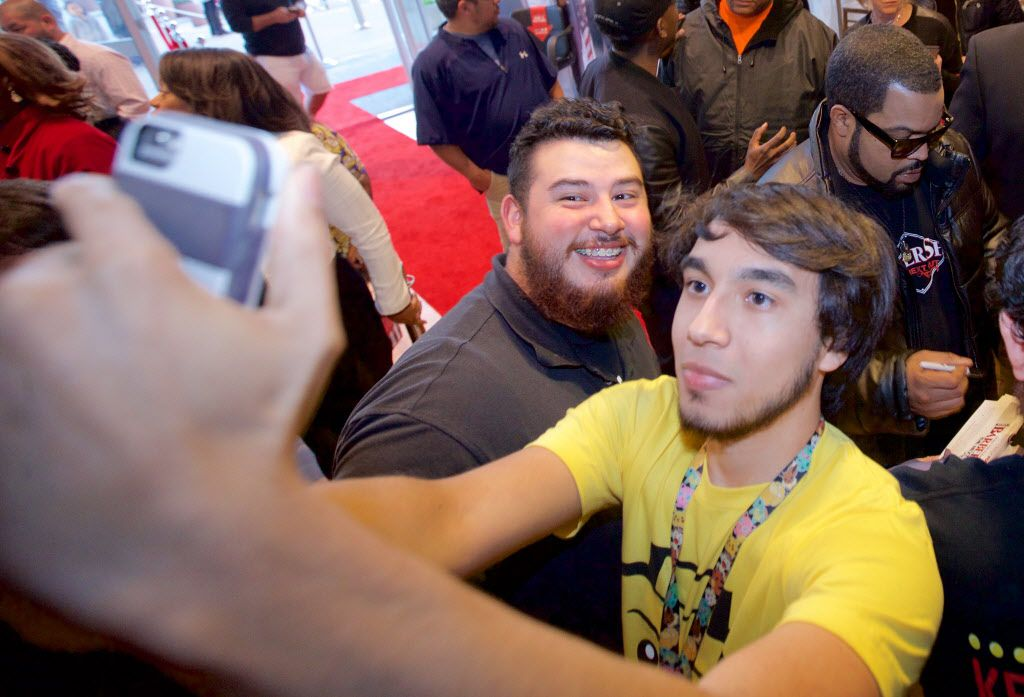 """Irving Marroquin, right, and Daniel Rocha, left, pose for a selfie with O'Shea Jackson, known by his stage name Ice Cube, in the background, before a screening of """"Barbershop, The Next Cut"""" at the Angelika Monday, March 21, 2016. (Brandon Wade/Special Contributor)"""