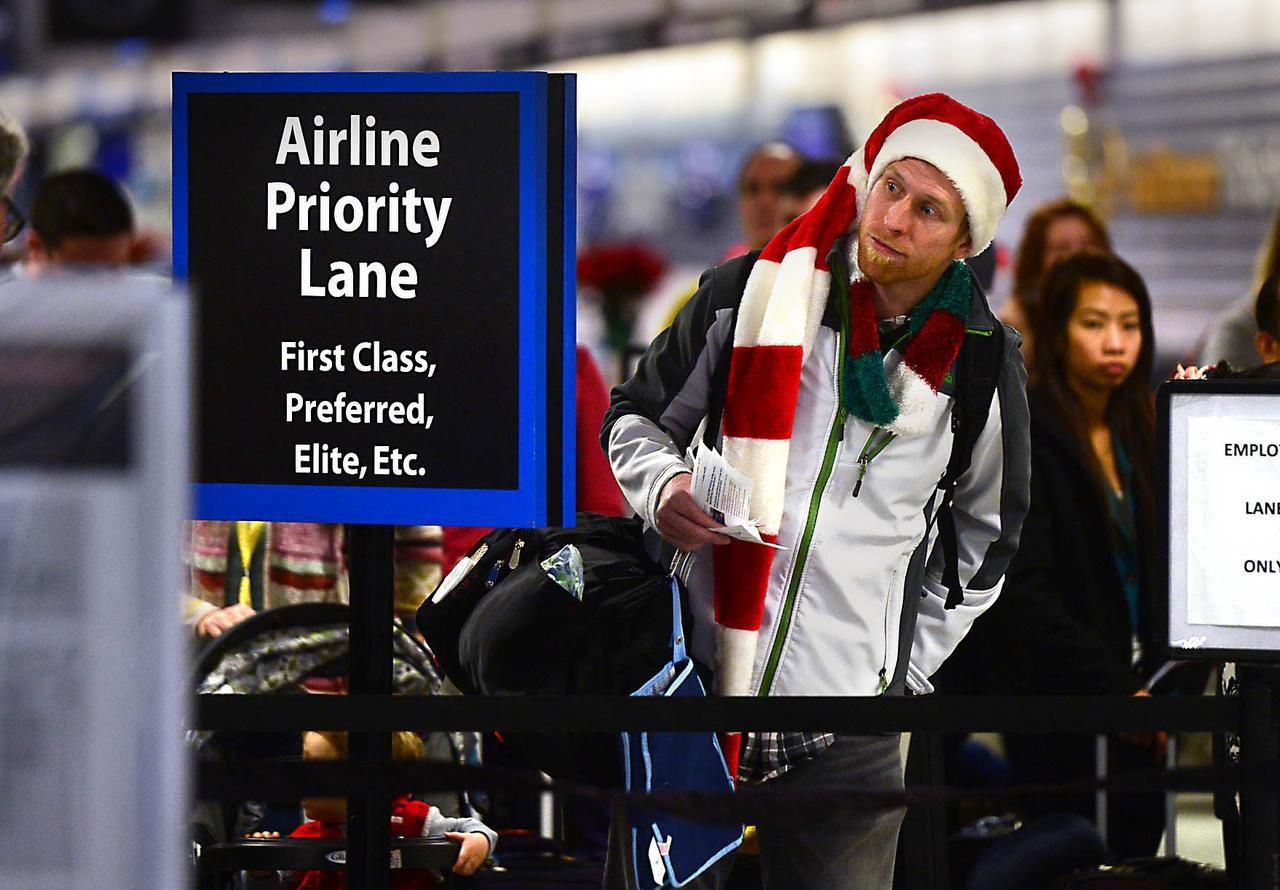 Amos Darnell hace fila en el aeropuerto de Charlotte, N.C., con espíritu navideño. Para viajar en Navidad, esta semana es cuando hay que comprar los boletos. (AP/TODD SUMLIN)