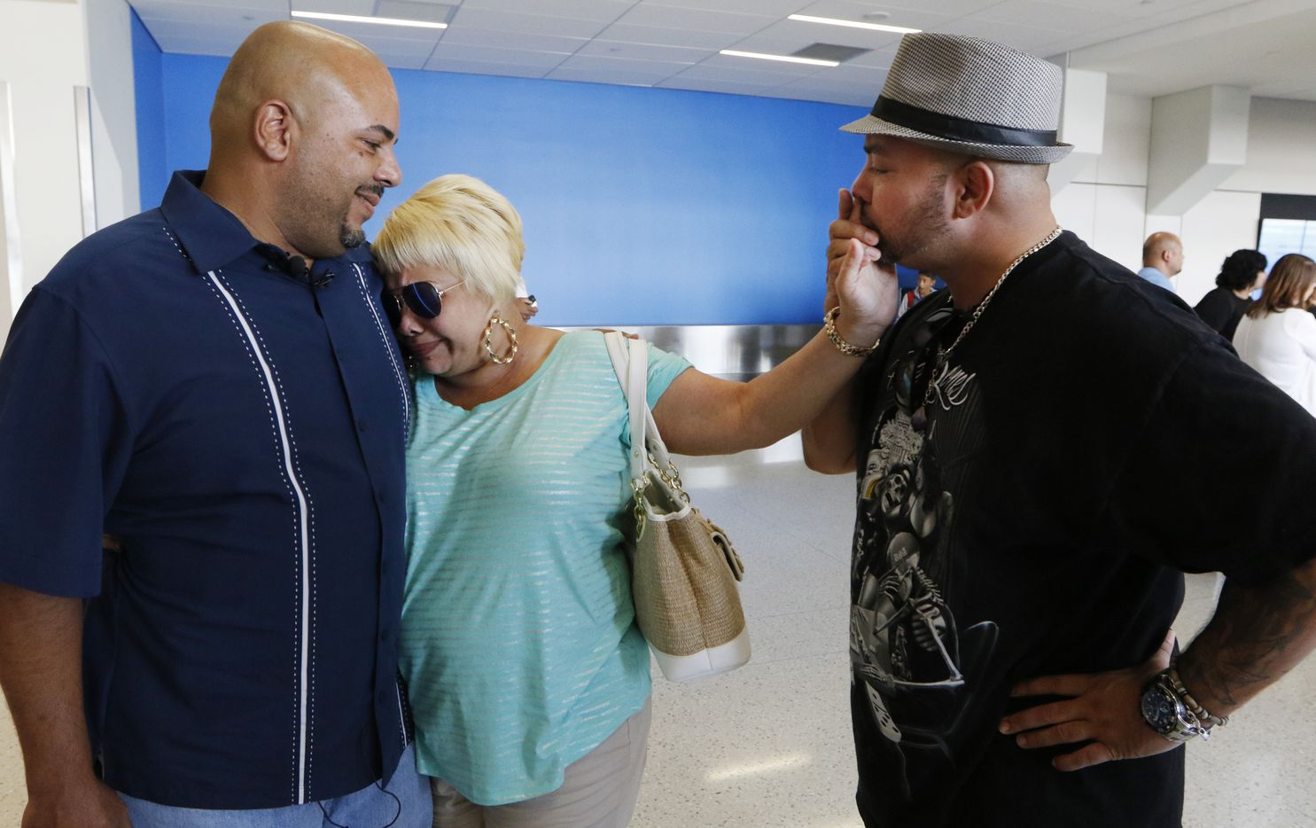 Anthony Wiggs (left) and Raymond Ramirez meet their biological mother, Elsie Ramirez, for the first time at DFW International Airport. The men were separated from their mother as infants, but a DNA search led them to her 46 years later.