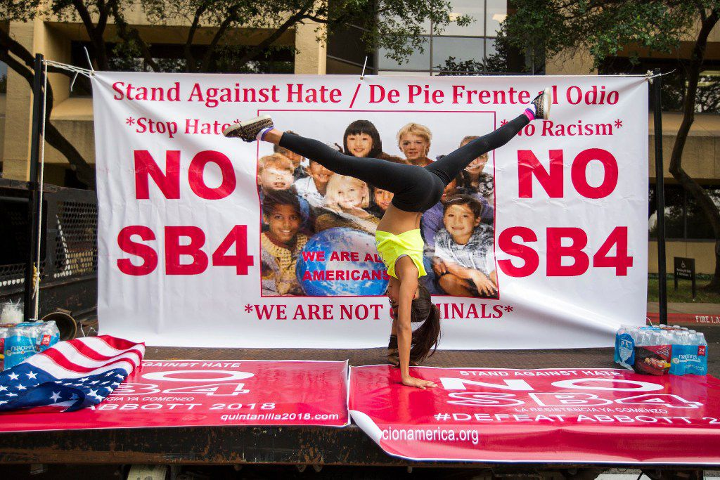 """Isabella Salinas, 10, does gymnastics in front of a sign in opposition to SB4 law, Texas' """"sanctuary city"""" legislation, as opponents rally outside the  offices of State Rep. Matt Rinaldi on Wednesday, May 31, 2017, in Farmers Branch, Texas."""