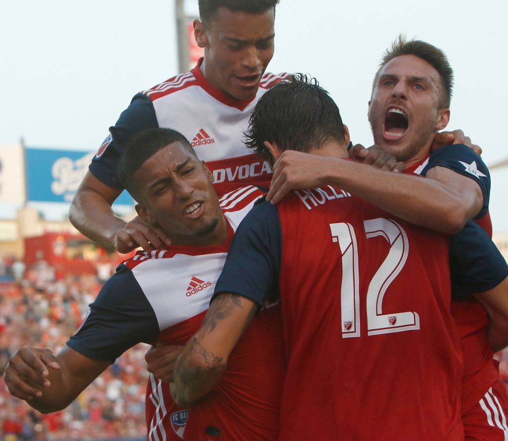 FC Dallas midfielder Santiago Mosquera (11), left, is mobbed by teammates Ryan Hollingshead (12), Brassan (4), right, and Brandon Servania (18), top after scoring during the first half of play against D.C. United. The two teams played their Major League Soccer game at Toyota Stadium in Frisco on July 4, 2019. (Steve Hamm/ Special Contributor)