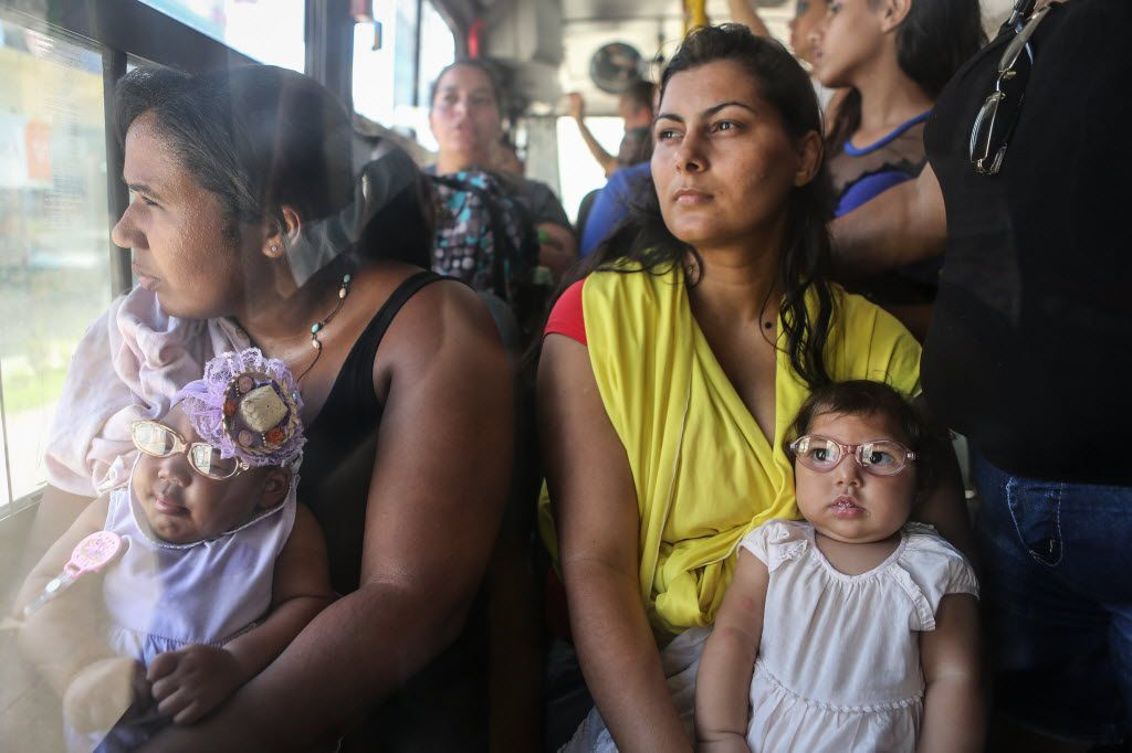 RECIFE, BRAZIL - JUNE 02:  Mother Jusikelly da Silva (R) holds her 7-month-old daughter Luhandra, who was born with microcephaly, as she wears her new glasses while riding a bus with another mother and infant born with microcephaly on June 2, 2016 in Recife, Brazil. Microcephaly is a birth defect linked to the Zika virus where infants are born with abnormally small heads. Some of these infants are also suffering from vision problems in Brazil. Mothers often must ride many hours on buses to take their children for medical visits. The Brazilian city of Recife and surrounding Pernambuco state remain the epicenter of the Zika virus outbreak, which has now spread to many countries in the Americas. A group of health experts recently called for the Rio 2016 Olympic Games to be postponed or cancelled due to the Zika threat but the WHO (World Health Organization) rejected the proposal.  (Photo by Mario Tama/Getty Images)