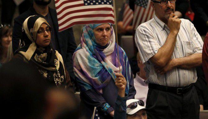 Aminah Hamed (centro) sostiene una bandera estadounidense durante la reunión del jueves del cabildo de Irving, donde un numeroso grupo de personas protestaron contra una resolución que consideran anti-musulmán. (DMN/ROSE BACA)