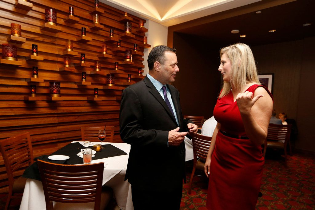 Ericka Downey (right) talks to Texas Tech coach Billy Gillispie during a Final Four party for coaches at Ruth's Chris at the Grand Hyatt Riverwalk in San Antonio, Texas on March 30, 2017.  Ericka Downey, the Oklahoma mother of two and wife of Northeastern State University basketball coach Mark Downey, told The Dallas Morning News that she received confirmation Thursday from the Mayo Clinic that she will be able to donate one of her kidneys to Billy Gillispie. (Nathan Hunsinger/The Dallas Morning News)