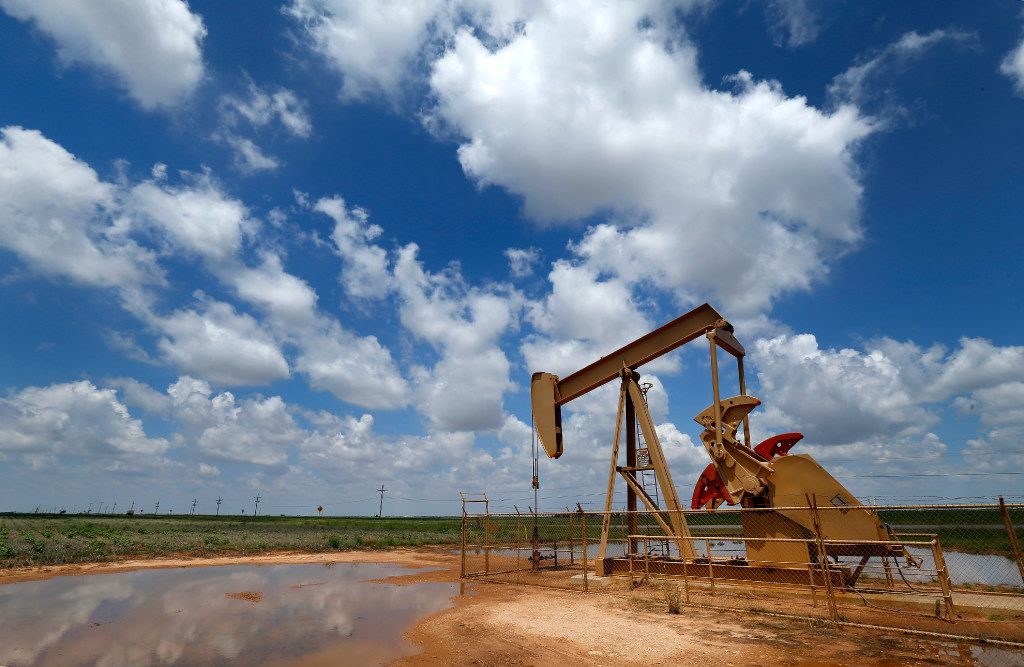 A pump jack draws oil north of Lubbock, Texas, Wednesday, August 2, 2017. (Tom Fox/The Dallas Morning News) Oil and Wind Stock