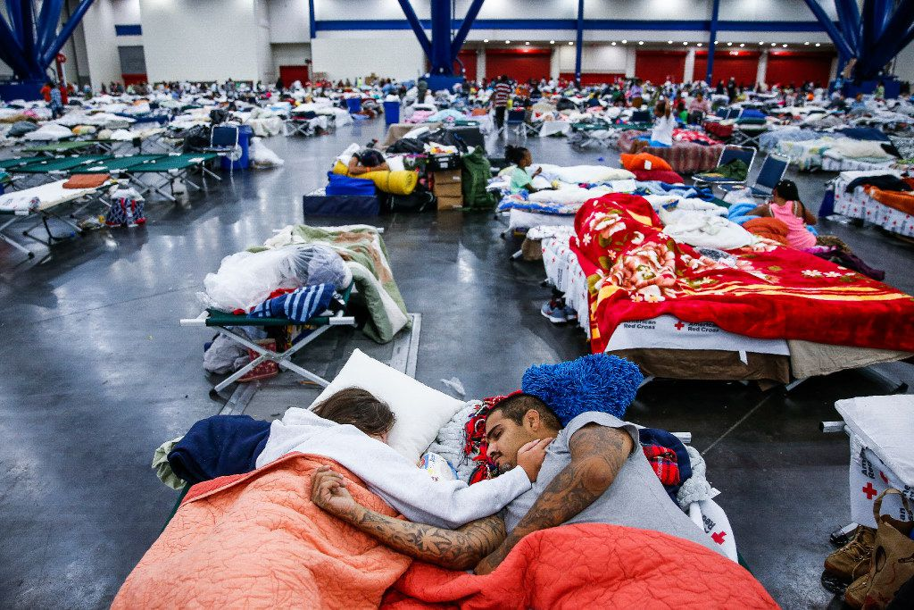 Tammy Dominguez and husband Christopher sleep on cots at the George R. Brown Convention Center, where nearly 10,000 people have taken shelter from the storm and flooding. The couple have been at the center since evacuating Houston's North Side on Sunday.