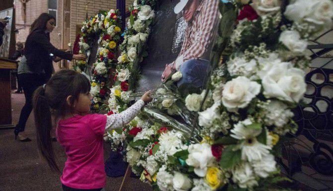Una niña deja flores durante un servicio funeral en Los Ángeles por la muerte del cantante Ariel Camacho. El joven músico falleció el mes pasado en un accidente de tránsito. (AP/RINGO H.W. CHIU)