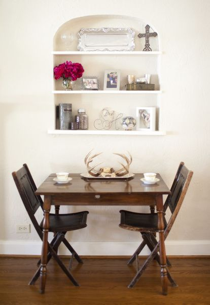 "To keep her home from ""getting too girly,"" Sarah Harmeyer added an antique table with leather-accented folding chairs under the arched built-in shelf."