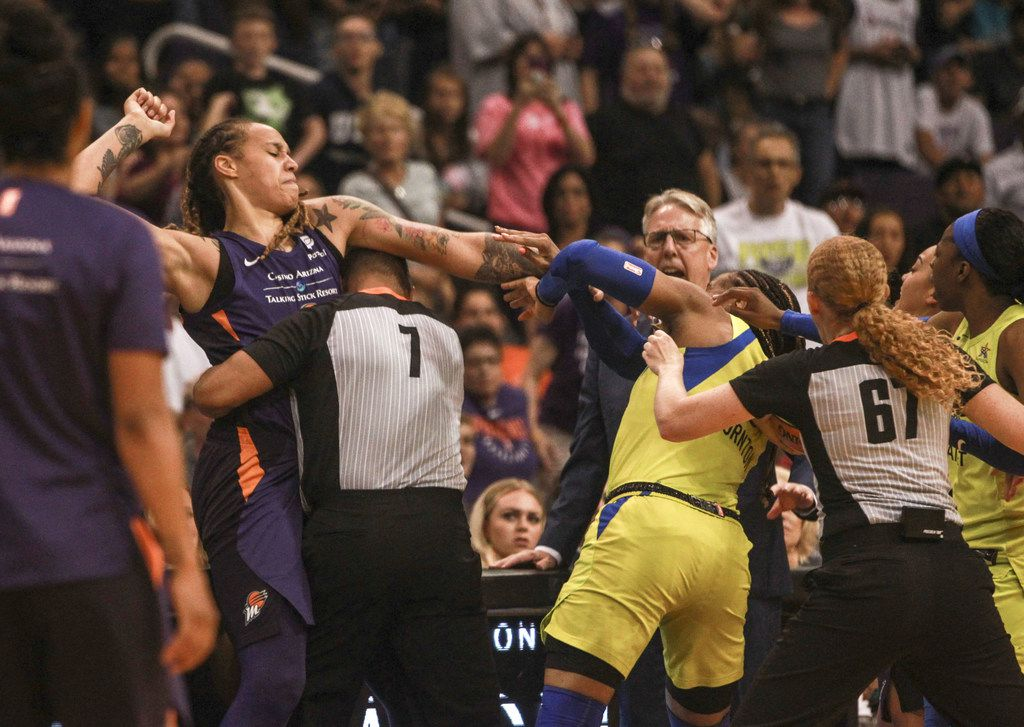 FOR USE IN THE DALLAS MORNING NEWS PRINT, ONLINE AND SOCIAL MEDIA ONLY. NO SHARING OR SALES BEYOND DMN -- Mercury center Brittney Griner (left, being restrained by an official) was ejected along with 5 other players, after a fight broke out halfway in the fourth quarter of the Phoenix Mercury against the Dallas Wings on August 10, 2019, at the Talking Stick Resort Arena in Phoenix, Ariz.