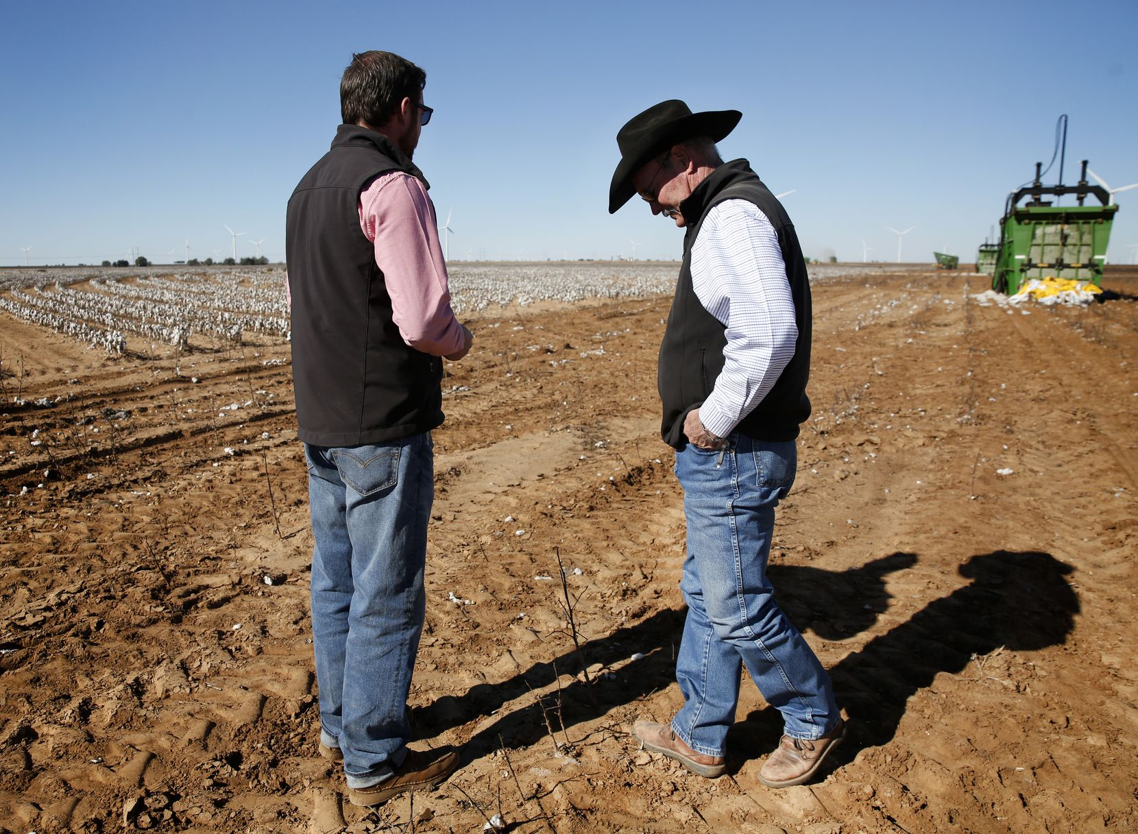 Matt Farmer (right) talks with his son-in-law Garron Morgan while workers harvest their cotton in Lynn County south of Lubbock.