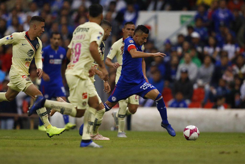 Roberto Alvarado (derecha) de Cruz Azul se desmarca con el balón frente a jugadores del América en un partido del torneo Apertura de México, el sábado 27 de octubre de 2018. (AP Foto/Eduardo Verdugo)