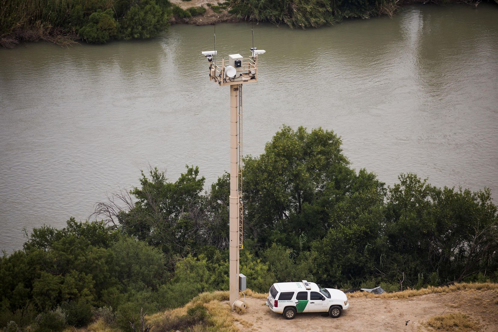 A U.S. Customs and Border Protection officer watches from a vehicle at the base of a camera tower on the banks of the Rio Grande River on May 10, 2017, near Rio Bravo, Texas, a few miles north of El Cenizo.